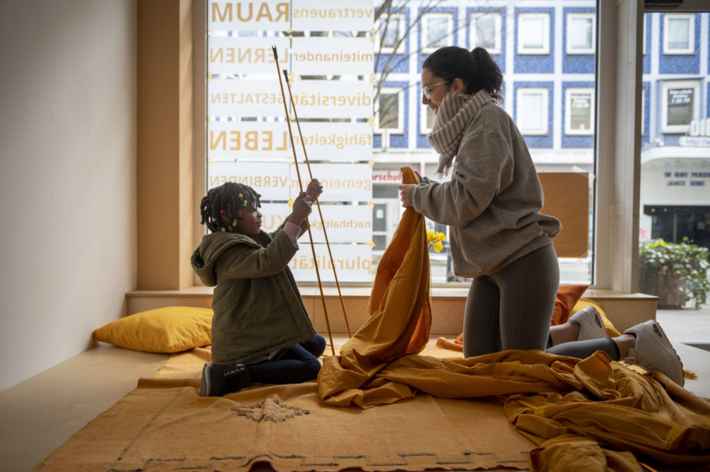 Ein Kind spielt mit einer Frau in den Räumlichkeiten von nouranour